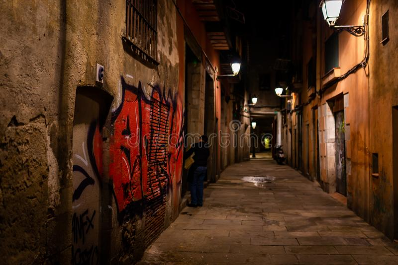 Small pedestrian street at night in the Barrio Gotico, Barcelona, Spain. Small pedestrian street at night in the Barrio Gotico, with red graffiti on one of the royalty free stock image