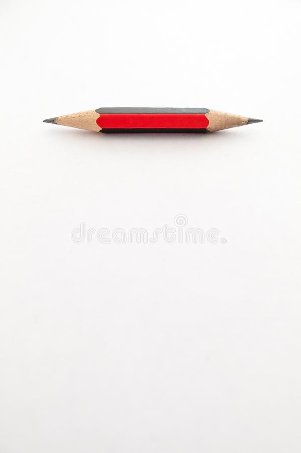 A small pencil, shap at both ends, on a white background stock photos