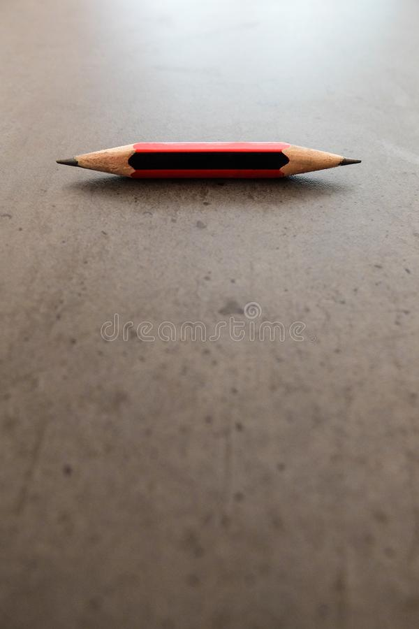 A small pencil, shapened at both ends, on a gray table. A small pencil, shapened at both ends, on a gray desk stock images