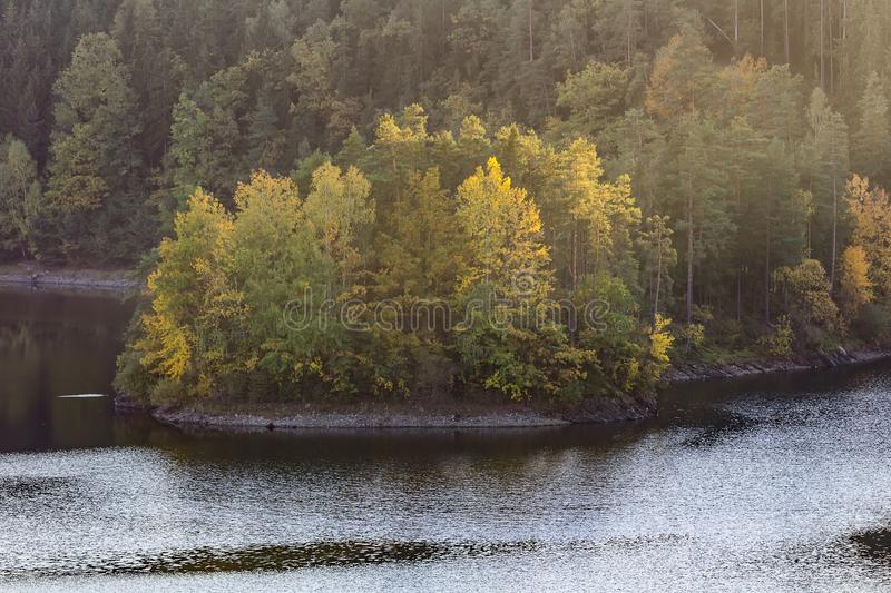 Small peninsula on dam Rimov with colorful trees, Czech landscape.  royalty free stock image