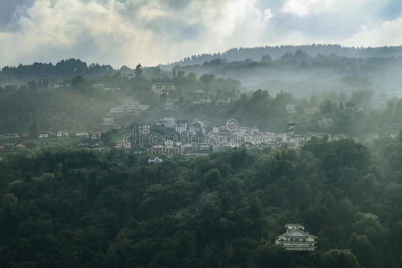 Small picturescue northern Italian village hiding in the mountain as morning fog rises up royalty free stock photos