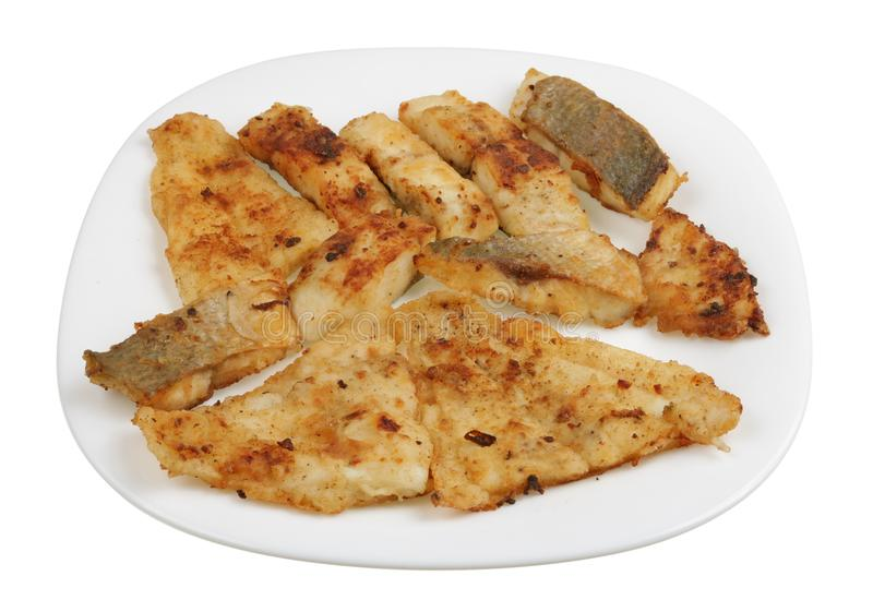 Small pieces of dorado fillet and flounder fish fried in olive oil without salt and spices isolated stock photo
