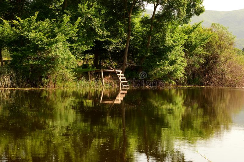 Small pier reflecting in water at Hutovo Blato nature reserve. Hutovo Blato is a nature reserve and bird reserve, located in south part of Bosnia and Herzegovina royalty free stock image