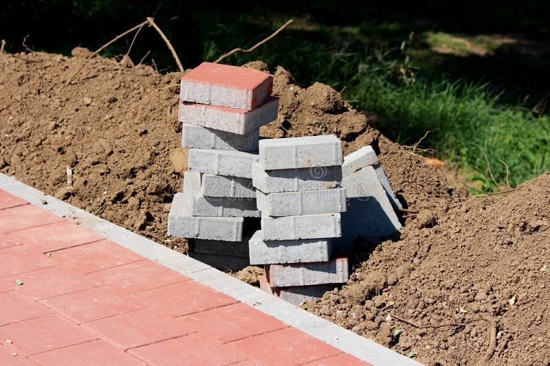 Small pile of grey and light red stone tiles next to sidewalk surrounded with dry soil and grass. At local public park stock photography