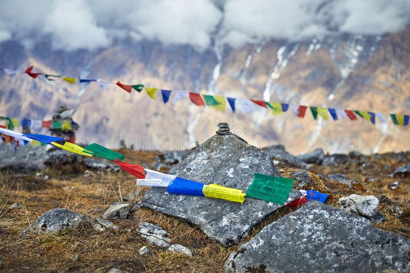 Landscape of Great Himalayas. Small piles from stones and Tibetan prayer flags Lung Ta at the Mardi Himal Base Camp at cloudy peaks of Himalaya Mountains in royalty free stock image