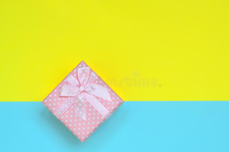 Small pink gift box lie on texture background of fashion pastel blue and yellow colors paper in minimal concept.  stock images