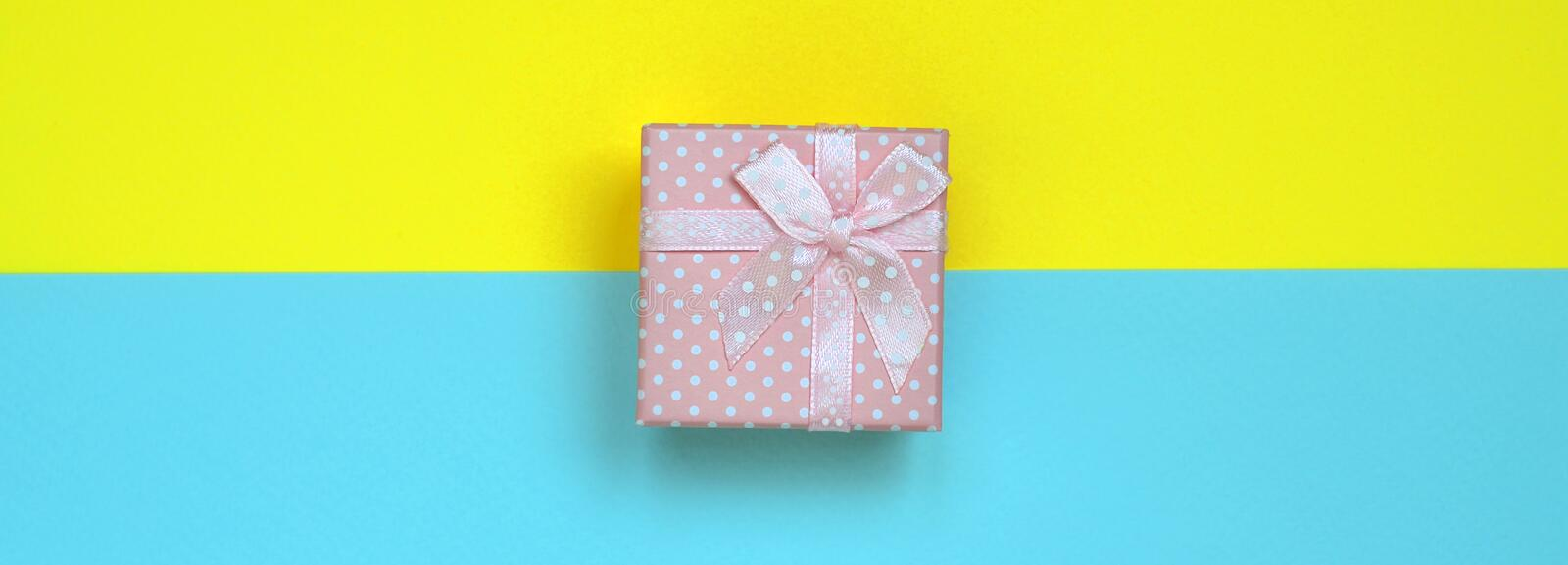 Small pink gift box lie on texture background of fashion pastel blue and yellow colors paper in minimal concept.  stock photos