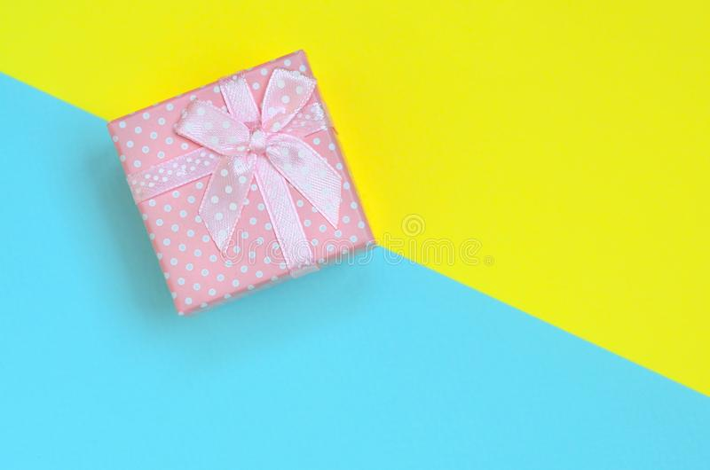 Small pink gift box lie on texture background of fashion pastel blue and yellow colors paper in minimal concept.  stock photography