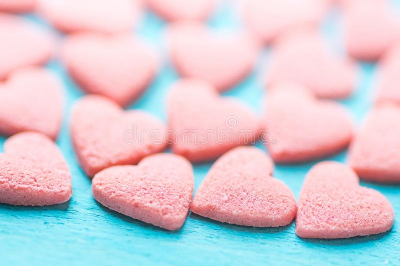 Small Pink Sugar Candy Sprinkles Spilled Scattered on Light Blue Background. Selective Focus. Pattern Template for Valentine royalty free stock photography