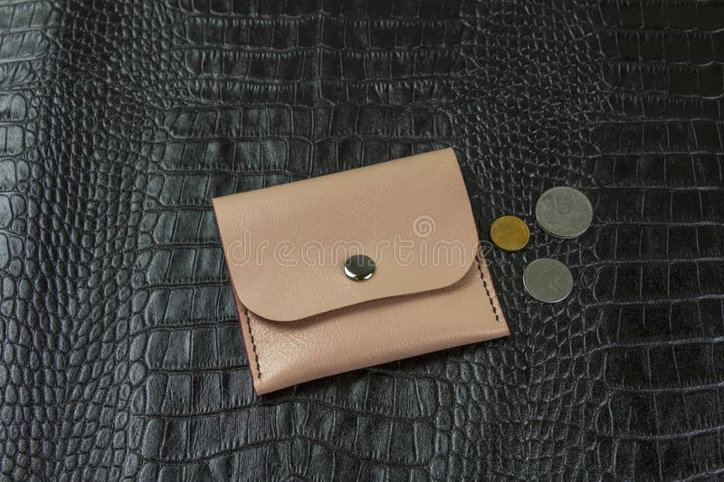 Small pink wallet with coins on black crocodile leather. A small pink wallet with coins on black crocodile leather stock photography