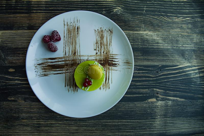 A small pistachio cake with a green coating and decorated with viburnum, confectionery dressing on a black background. Side view stock photo