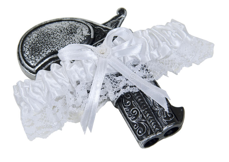 Small Pistol in a Garter belt. Little black pistol in a garter belt made of lace and ribbon worn as a decorative accessory - path included stock image