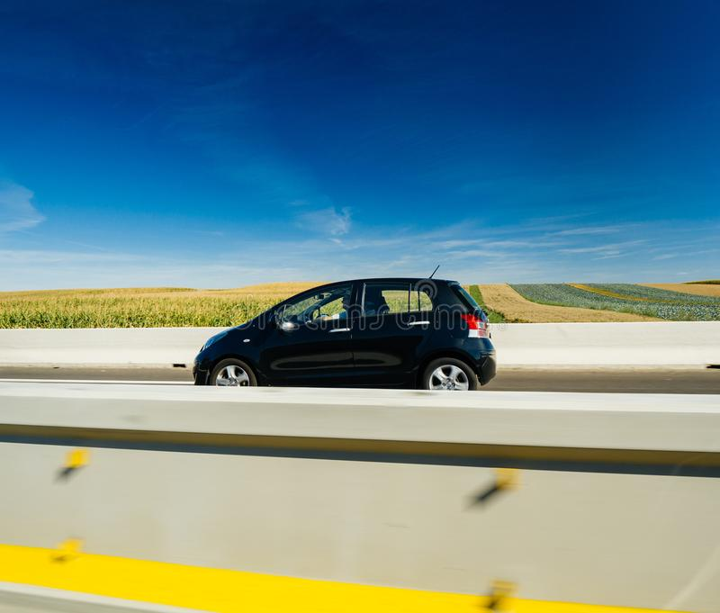 Small 4 place electric Toyota car driving fast stock photography