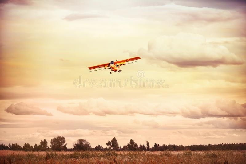 A small plane flying in the sky over the fields and forests. stock photography