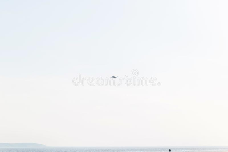 A small plane in the sky. Low-flying aircraft over the coast stock photography