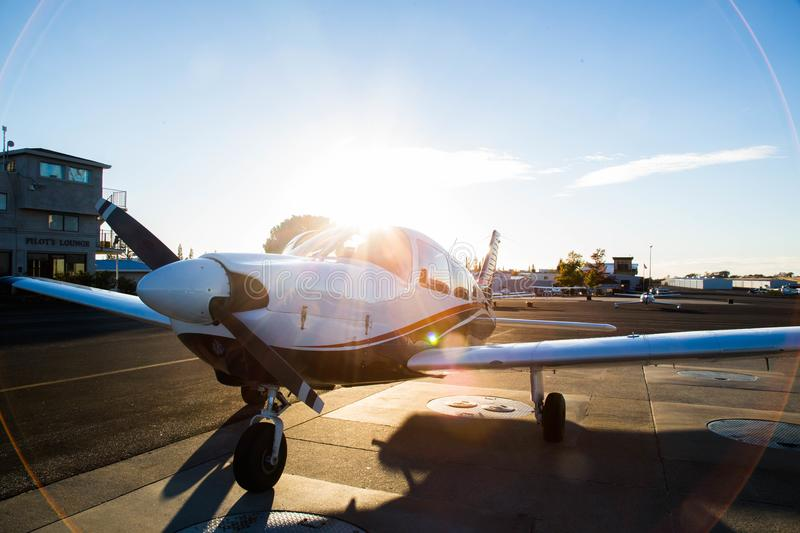 Small Plane With Sunset. Small plane sitting on the tarmac in front of a beaming sunset stock photos