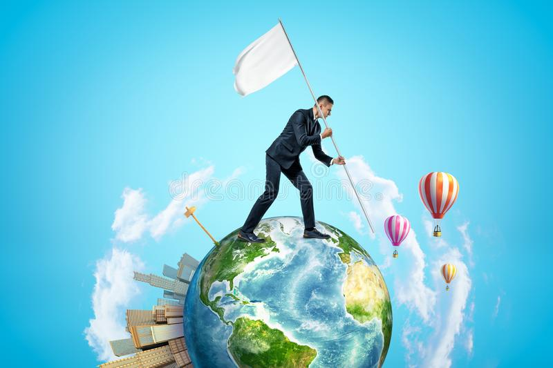 Small planet Earth with modern city popping up on one side and hot-air balloons flying in sky, and businessman walking. On planet and carrying white flag. Start stock photography