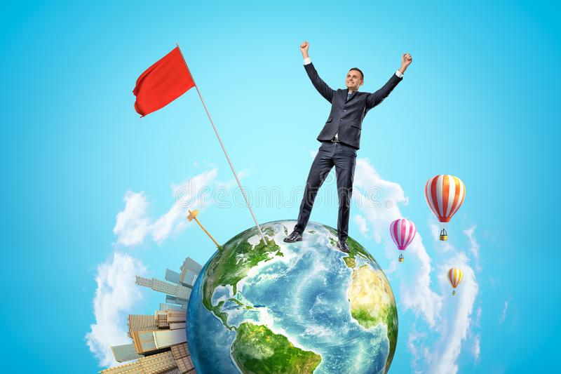 Small planet Earth with modern city popping up on one side and hot-air balloons flying in sky, and happy businessman who. Has planted red flag on planet. Be royalty free stock photo