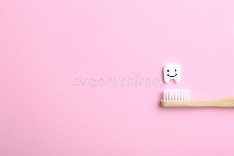 Small plastic tooth, wooden brush and space for text on color background royalty free stock photos