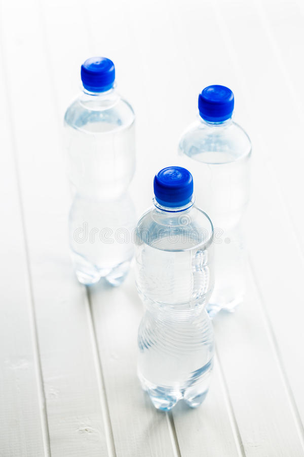 Small plastic water bottle. Small plastic water bottle on white table stock photos