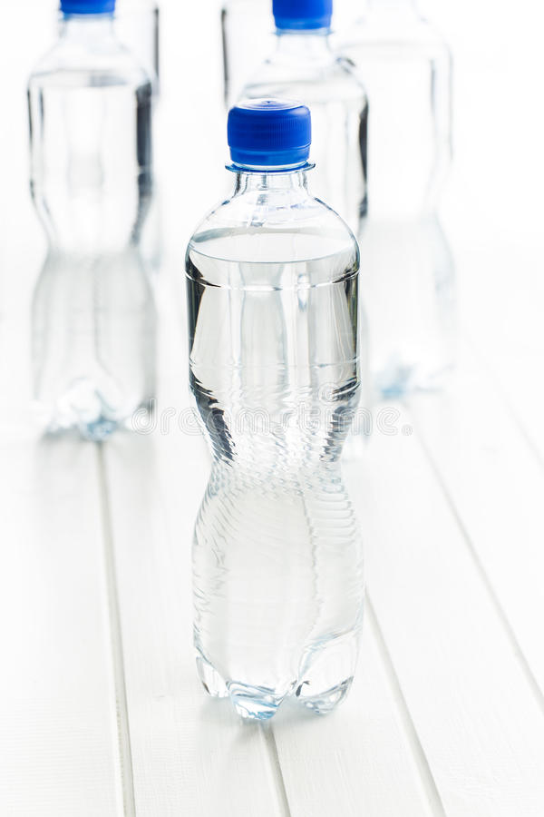 Small plastic water bottle. Small plastic water bottle on white table royalty free stock photos