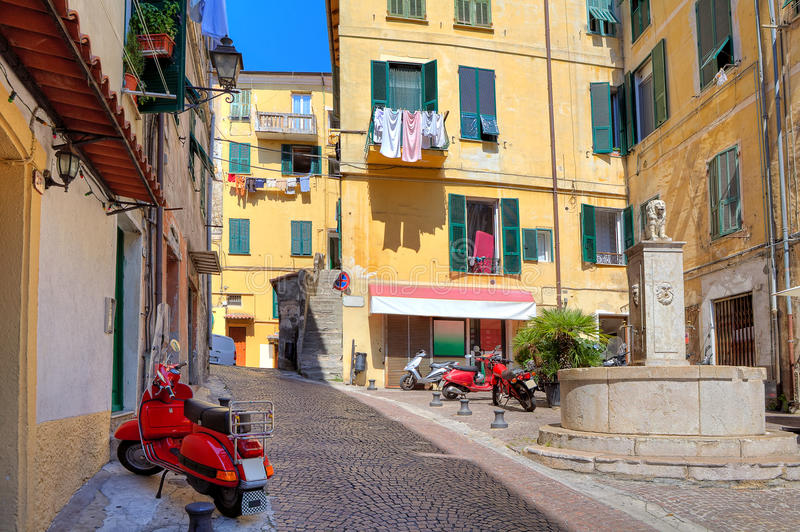 Small plaza among colorful houses in Ventimiglia, Italy. Typical view of small cobblestone street with scooters among old colorful residential buildings in town stock image