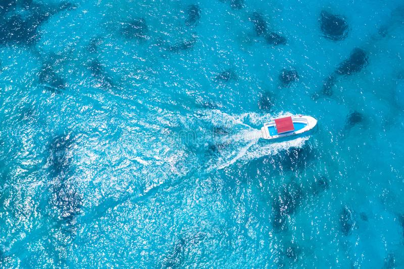 Small pleasure boat in a paradise bay of a tropical ocean, top aerial view royalty free stock photo