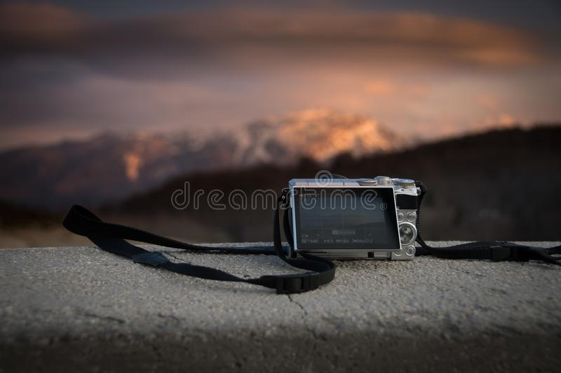 Small pockect size digital camera photographing sunset over mountains stock image
