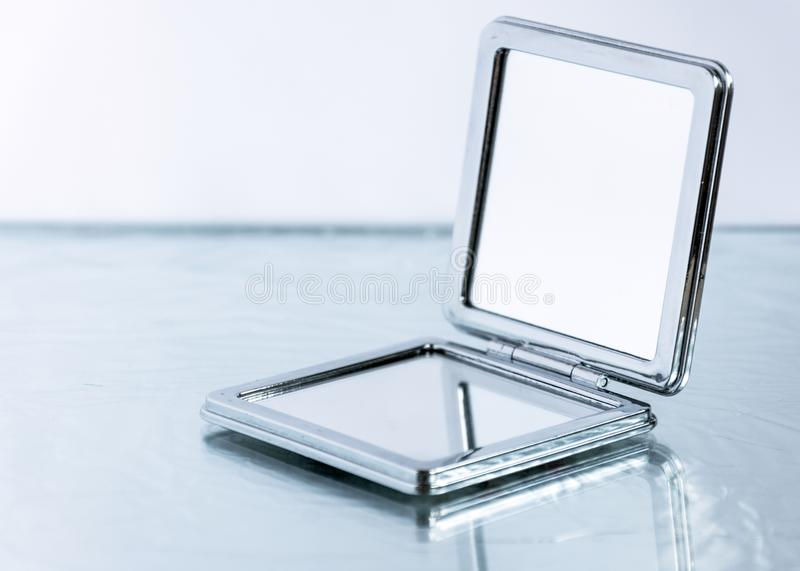 Small pocket mirror on glass table background. stock image