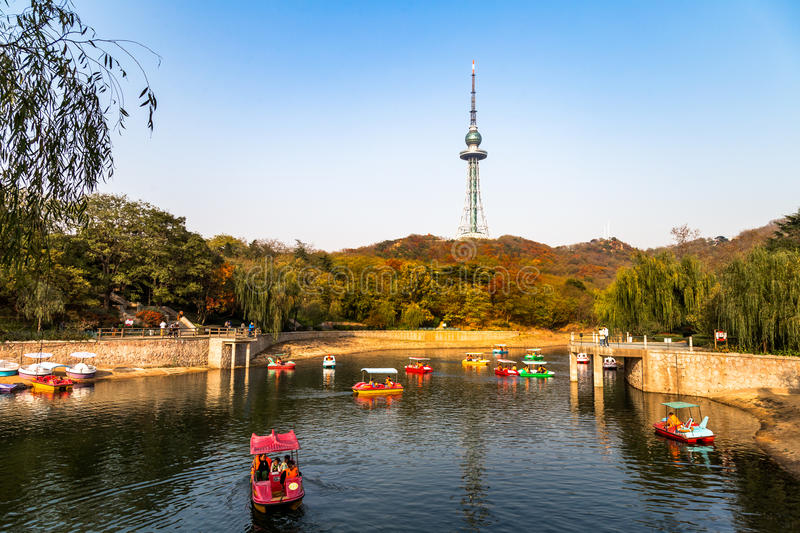 Small pond with boats in Zhongshan Park in Autumn, Qingdao, China. The TV tower is in the background, and the hills are covered in red leaves royalty free stock images