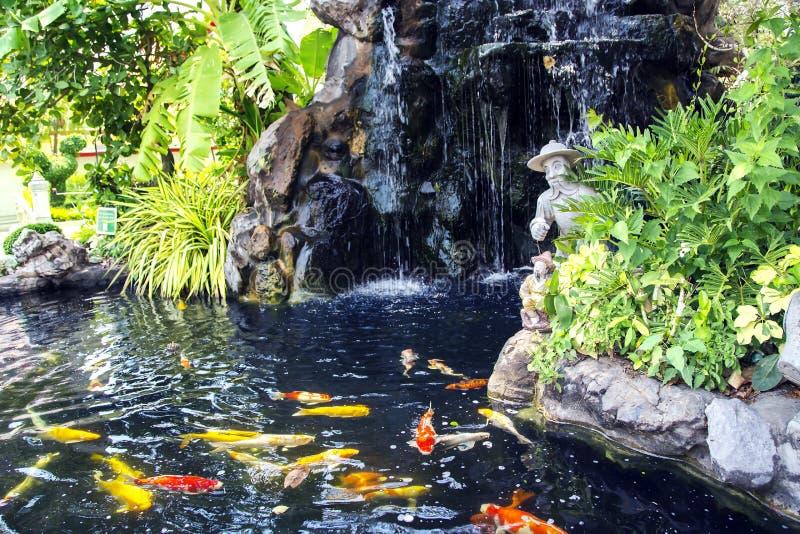 Small pond with a waterfall and koi carps fish. At Wat Phra Kaew, Emerald Buddha Temple, Bangkok, Thailand royalty free stock photo