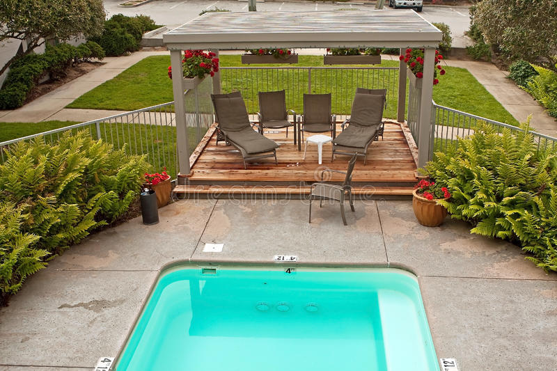 Small pool and wood deck and greenery. A small pool or jacuzzi surrounded by patio and boston ferns and wood deck with lawn chairs. Red geraniums with showy red stock image