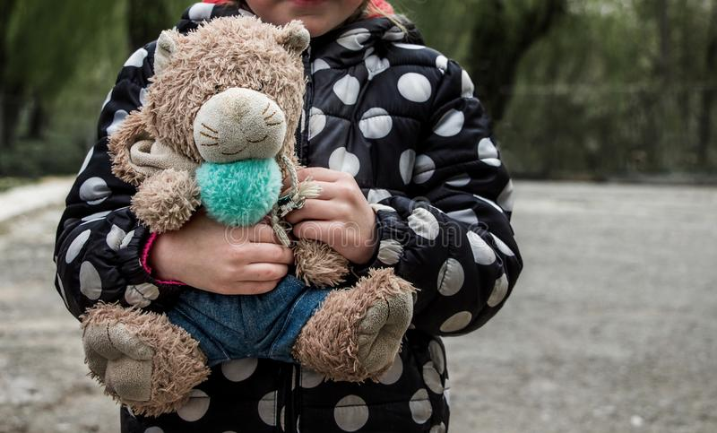 A small poor girl holds in the hands of an old teddy bear_. A small poor girl holds in the hands of an old teddy bear royalty free stock photos