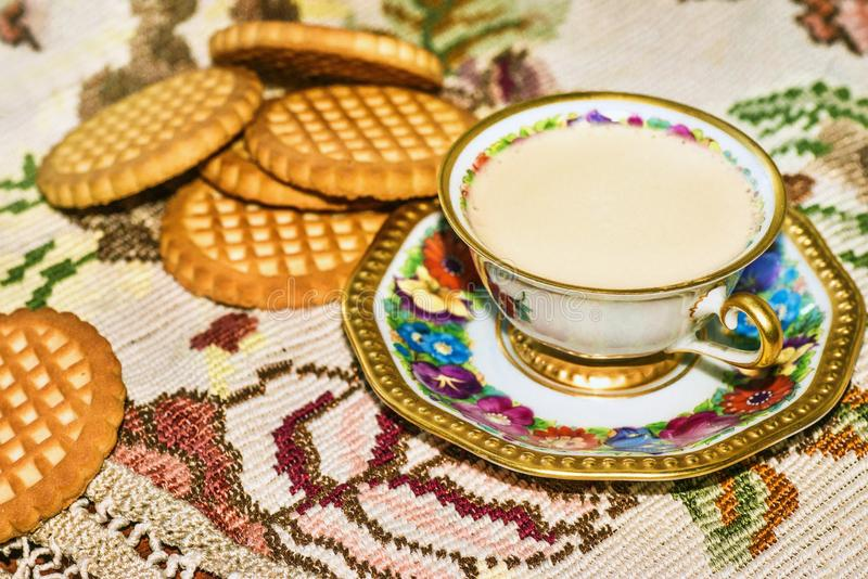 Small porcelain cup with white coffee and biscuits on embroided tablecloth. Small old-time flowered porcelain coffee cup with biscuits on embroidered lace stock image