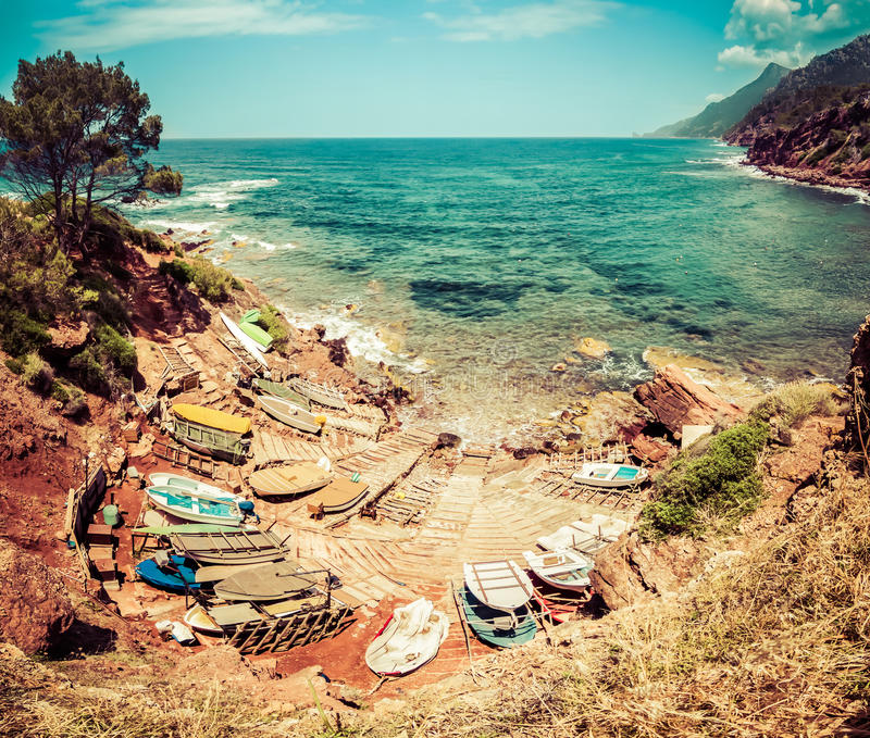 Small port with fishing boats. View to blue sea, mountains. royalty free stock images