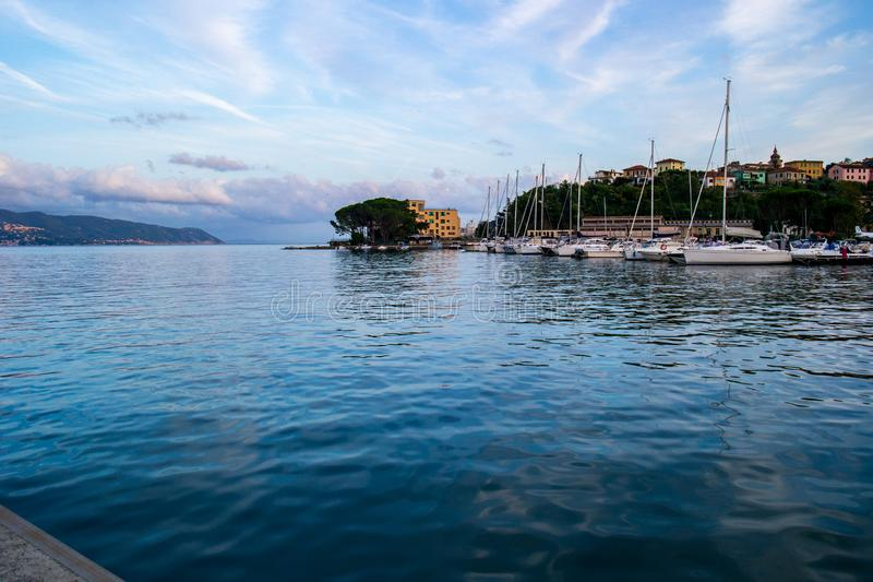 Small port on the mediterranean sea in an Italian village with docked sail boats on a sunny summer day stock photography