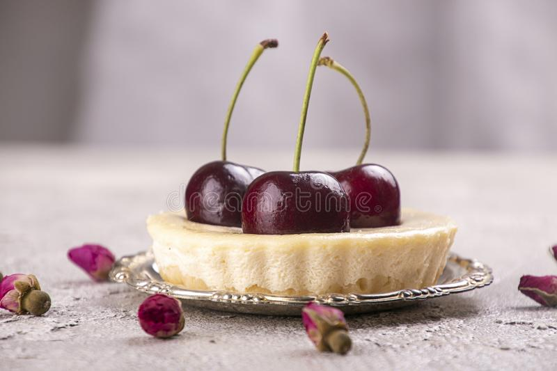 Small portion cheesecake with fresh sweet cherries against of gray background royalty free stock image