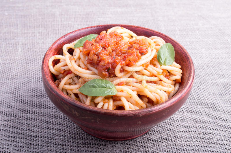 Small portion of cooked spaghetti in a brown small wooden bowl royalty free stock photography