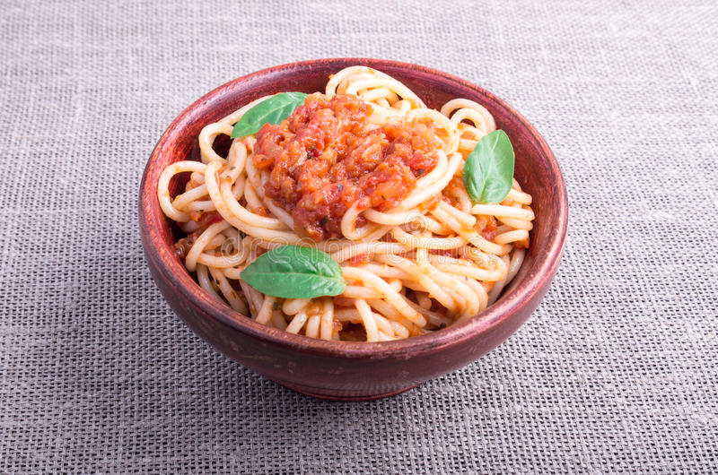 Small portion of cooked spaghetti with tomato relish closeup. Small portion of cooked spaghetti with tomato relish and basil leaves in a brown small wooden bowl stock images