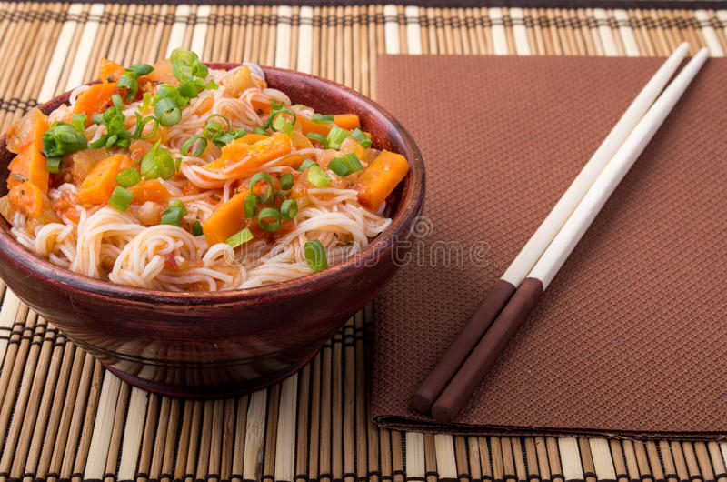 Small portion of rice vermicelli hu-teu with vegetable sauce. Of carrots in a small brown wooden bowl closeup on striped mat near chopsticks royalty free stock photography
