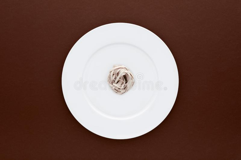 Small portion of tagliatelle pasta on round white plate on brown background. Concept of dieting, healthy and less eating stock photo