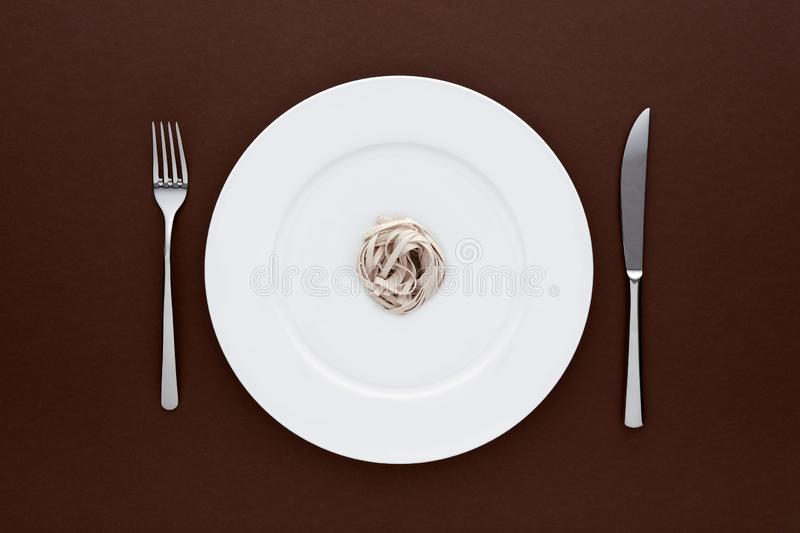 Small portion of tagliatelle pasta on round white plate with fork and knife on dark brown tablecloth. Concept of dieting and healthy eating royalty free stock photo