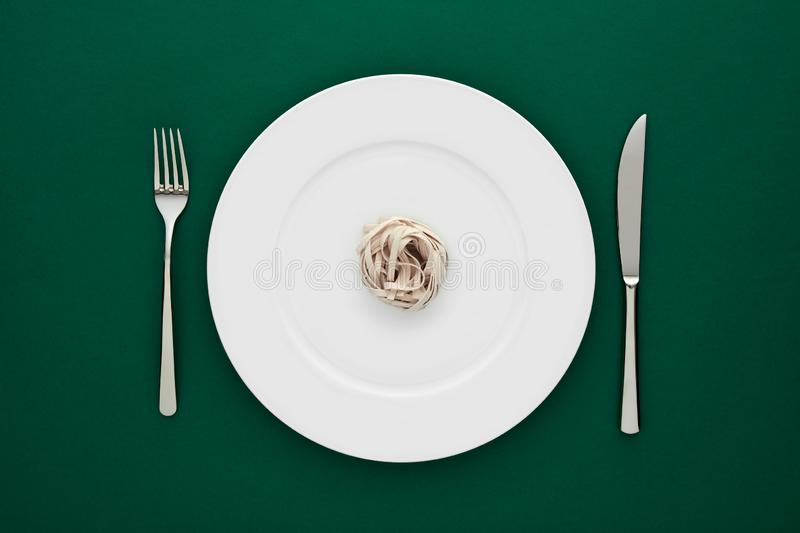 Small portion of tagliatelle pasta on round white plate with fork and knife on green tablecloth. Concept of diet, health and eating less stock photography