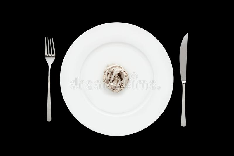 Small portion of tagliatelle pasta on round white plate with fork and knife on isolated black background. Concept of dieting and healthy eating royalty free stock photos