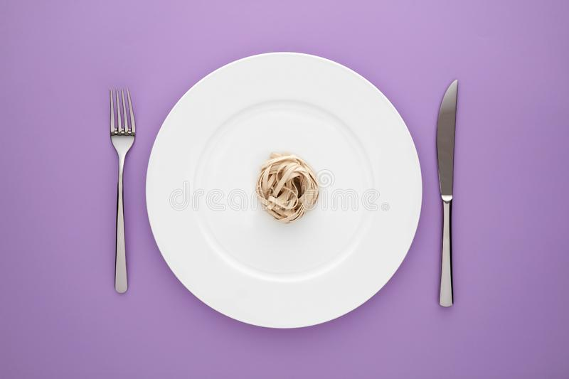 Small portion of tagliatelle pasta on round white plate with fork and knife on light purple tablecloth. Concept of diet, health and eating less royalty free stock photos
