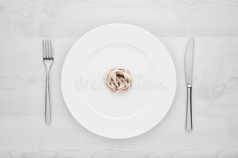Small portion of tagliatelle pasta on round white plate with fork and knife on a white wooden table. Concept of diet, health and eating less royalty free stock images