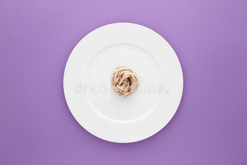 Small portion of tagliatelle pasta on round white plate on light purple background. Concept of diet, health and eating less stock photo