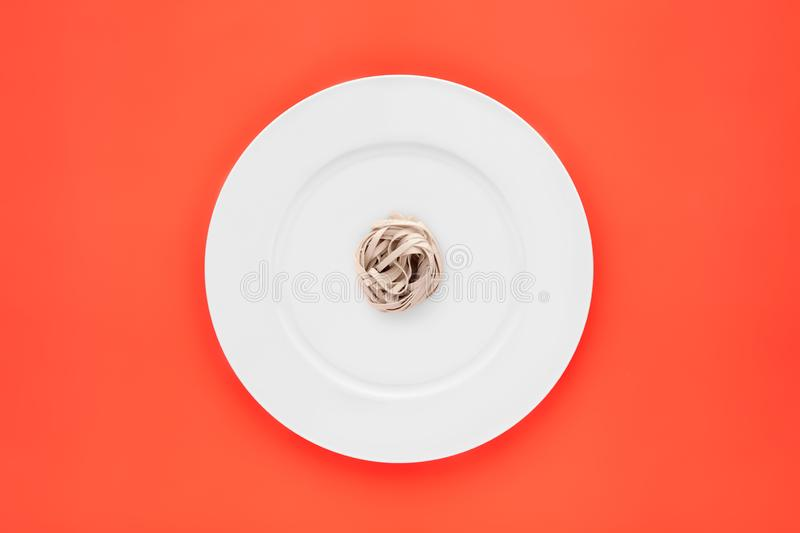 Small portion of tagliatelle pasta on round white plate on orange background. Concept of diet, health and eating less stock images