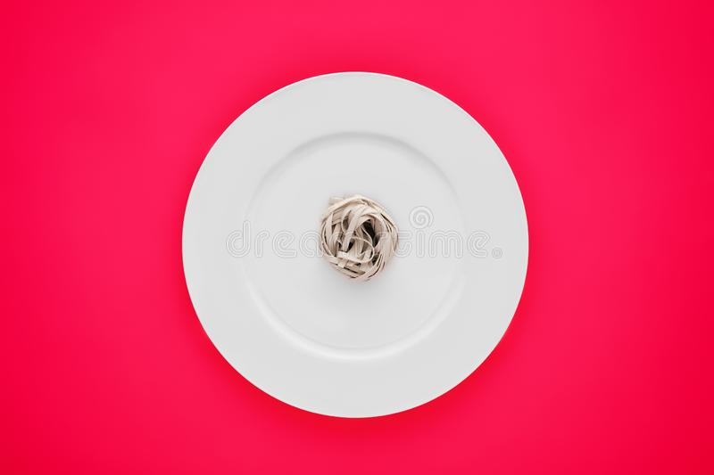 Small portion of tagliatelle pasta on round white plate on pink tablecloth. Concept of diet, health and eating less stock photo