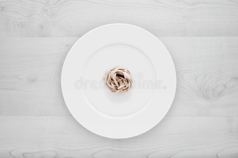 Small portion of tagliatelle pasta on round white plate on a white wooden table. Concept of dieting, healthy and less eating. Small portion of tagliatelle pasta royalty free stock photos